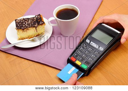 Use payment terminal and credit card for paying in cafe or restaurant cheesecake and coffee enter personal identification number finance concept
