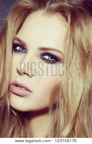 Vintage style close-up portrait of young beautiful blonde woman with smoky eyes make-up