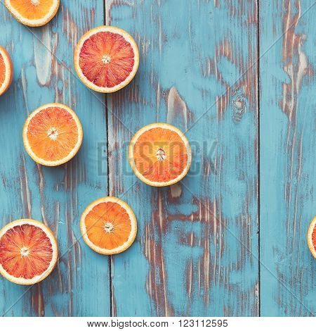 Fresh  blood orange halves on turquoise board. Top view, vintage toned image, blank space