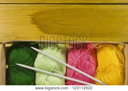 different colored skeins of yarn and knitting needles with copy space.