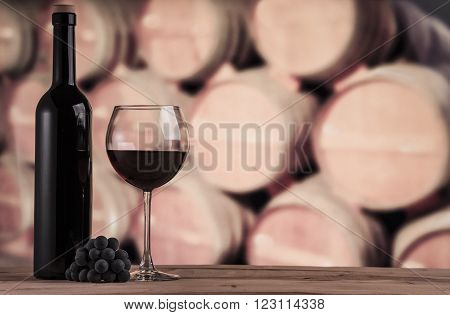Wine barrels in the wine cellar. One glass of red wine with bottle on the wooden table