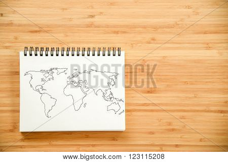 World map outline sketch on paper of binder notebook that placed on wooden floor background - can use for travel business or save the earth concepts