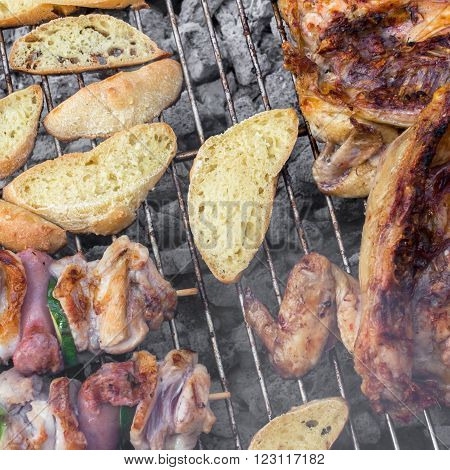 Skewer chicken pieces half cockerel and slices of bread on the grill and smoke.