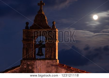 Full moon night on the steeple of a church town of Lastres Asturias Spain