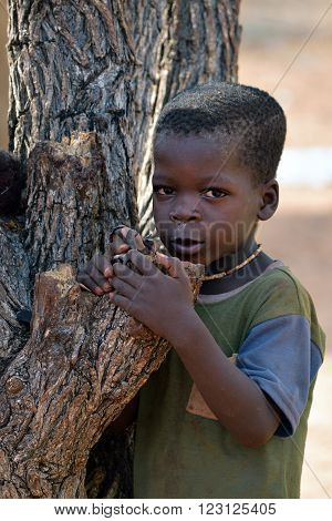 KAMANJAB NAMIBIA - FEB 1 2016: Little unidentified Himba boy shown in himba tribe village