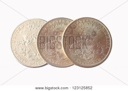 Three US American gold eagle one dollar coins on a white background