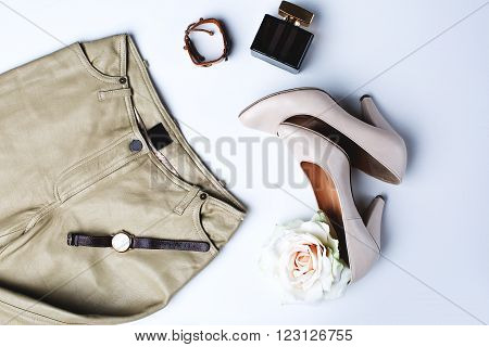 female accessories. Beige shoes with perfume and watches