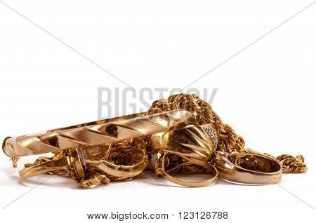 scrap gold jewellery including chains, bracelets and rings on a white background