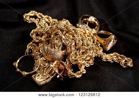 scrap gold jewellery including chains bracelets and rings on a black background
