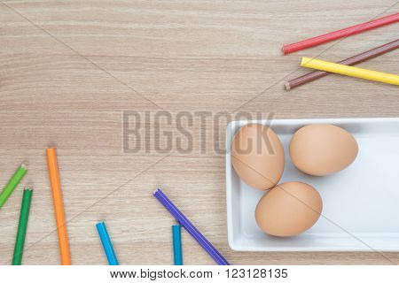 Three eggs in white plate with color pencils on wooden surface ready for Easter painting with space for text