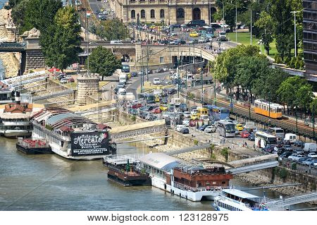 BUDAPEST, HUNGARY, JULY 10, 2015: Heavy traffic at the coastline of Danube River, touristic boat restaurants and facilities can be seen.