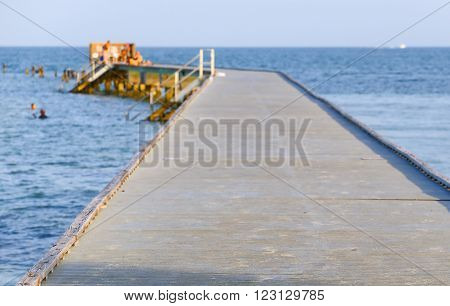 Higgs Beach Pier in Key West sticking out in the ocean with ladders leading into the water. Some people are sitting and standing on the pier or swimming next to it