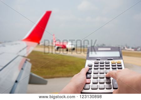Travel Cost Calculation Concept By Calculator And Airplane In Background