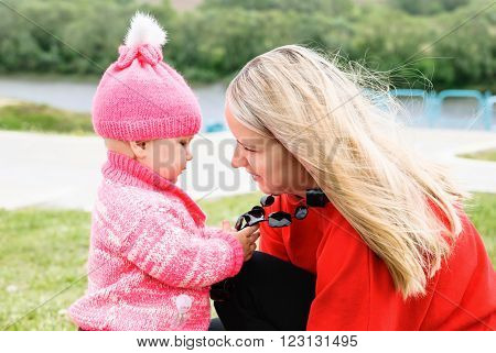 Girl playing with beads on her mother squatting on his haunches