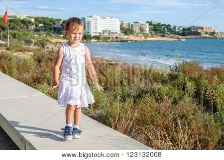 The girl goes on a high curb stone against the sea and bushes