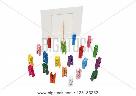 Green clothespin standing in front of a white frame and displays it on a toothpick. Many other multi-colored pegs are around