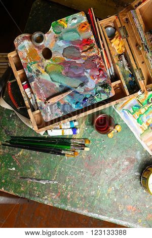 Workplace of the artist with brushes, oil paints, pallete, palette knife and tea