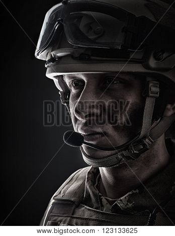 Young handsome military man in italian camouflage wearing helmet glasses and radio set