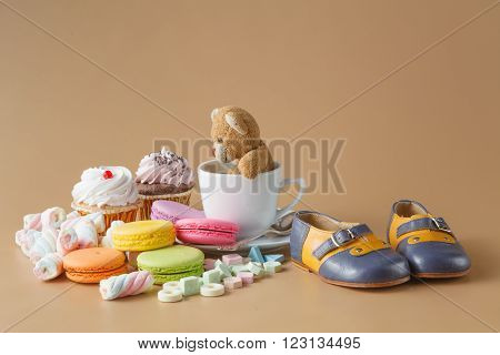Macaroons, Marshmallows, Cakepops, Bear Toy And Other Sweets On Beige Background At Kids Birthday Pa