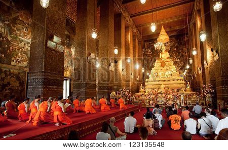 BANGKOK, THAILAND - FEB 14: People praying with monks of historical monastery Wat Pho on February 14, 2015. Wat Pho is a large Buddhist temple complex founded in 16th century