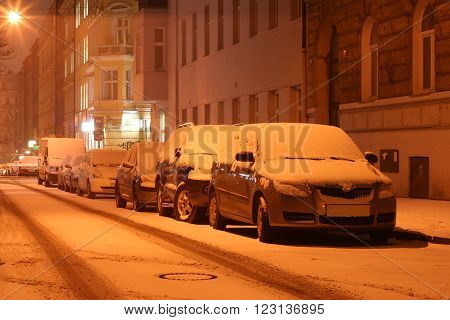 Winter city center street at night with parked cars covered by fresh white snow. Detail on one car. Light with magic rays. New Town Prague January 2016