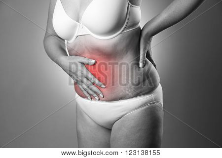 Woman in a white bra and white panties with abdominal pain on a gray background. Black and white photo with red dot