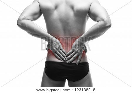 Man with backache. Muscular male body. Handsome bodybuilder posing in studio. Isolated on white background with red dot. Black and white photography