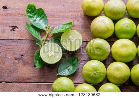 Green Lemons with leaves on hard wood