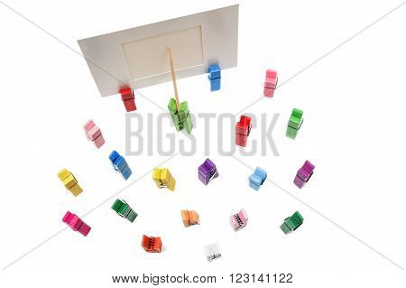 Green clothespin standing in front of a white frame and displays it on a toothpick. Many other multi-colored pegs are around. View from above