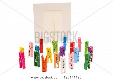 Green clothespin standing in front of a white frame and displays it on a toothpick. Other pegs grouped together