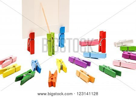 Clothespin is shows a toothpick on a white frame. Other multi-colored pegs arranged in a semicircle.One is standing