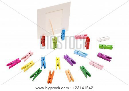 Clothespin is shows a toothpick on a white frame. Other pegs arranged in a semicircle.One is standing