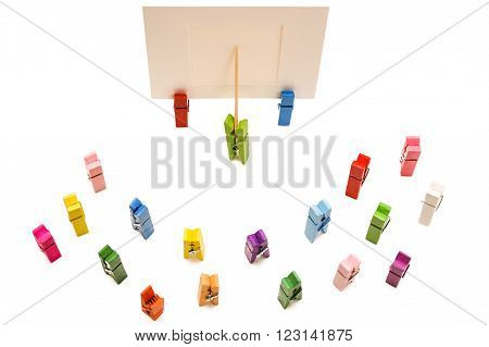 Green clothespin standing in front of a white frame and displays it on a toothpick.Other colored pegs are around