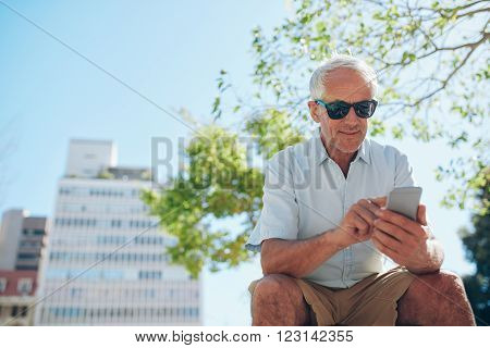 Mature Man Sitting Outdoors Using Mobile Phone