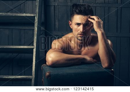 Handsome sexy sensual muscular stylish young man topless with bare torso and beautiful body sitting near stairs with hard big retro suit case indoor on wooden background, horizontal picture