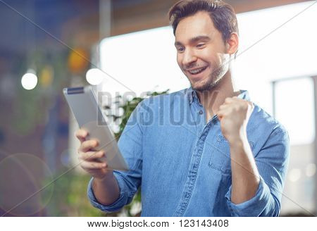 I am the winner. Positive  pleasant handsome man  holding tablet and using it while expressing jubilation
