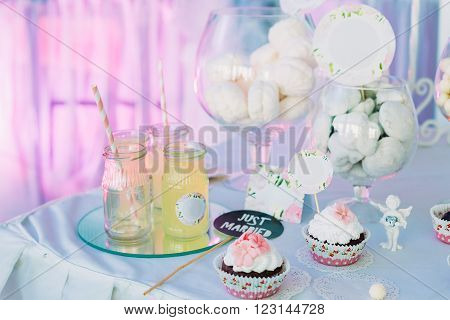 Dessert Sweet Tasty Cupcakes, Lemonade and Marshmallow In Candy Bar On Table. Delicious Sweet Buffet. Bright Wedding Decorations