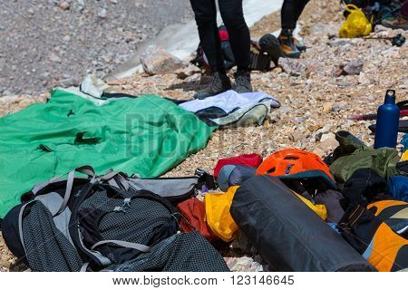 Heap of Dropped in Mess Mountain Climbing and Camping Equipment Backpack Helmet Sleeping Bag Boots Thermos Flask and Other Legs of People Blurred Behind