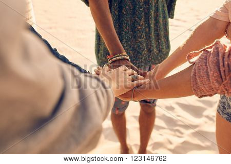 Friends at the beach putting hands together. Multiracial group of young people with hands in stack at the beach.