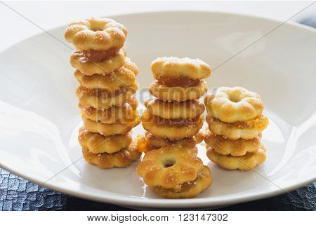 Sweet crispy pineapple biscuit and cookie scatter over with sweet sugar in white plain plate ready to eat Sweet crispy pineapple biscuit with sugar in row
