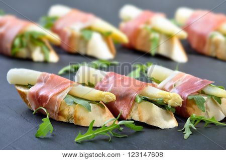 Dainty morsels with white asparagus on rocket leaves wrapped with Italian prosciutto