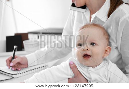 Cute baby boy on businesswoman's hands at home