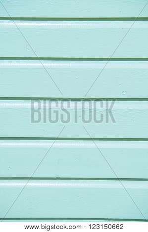 Closeup of bright empty wooden clapboard textured siding painted in light blue color with horizontal lines and nobody copy space vertical picture