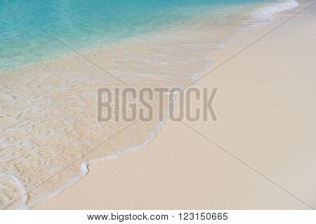Closeup of clean foamy sea water wave on wet sand of ocean beach surf with no people sunny day outdoor, horizontal picture