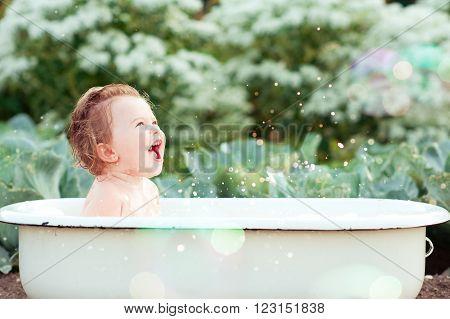 Laughing baby girl taking bath outdoors. Happy child. Childhood.