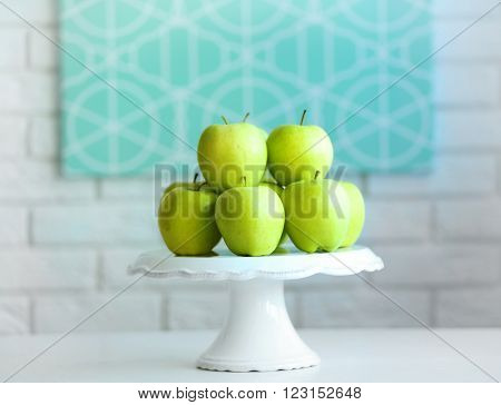 Ripe green apples on a stand in kitchen
