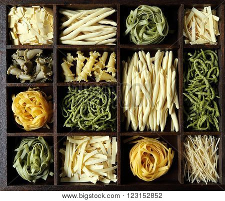 Different kinds of pasta in a wooden box.
