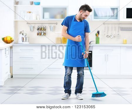 Man sweeping floor in the kitchen