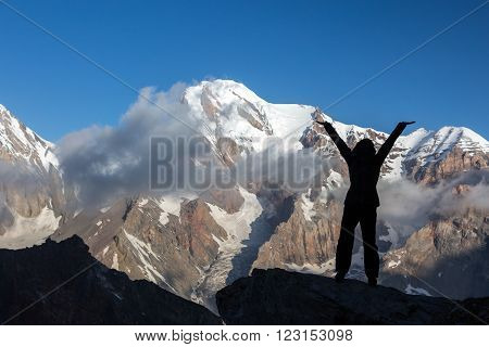 Silhouette Woman Staying on Top of Rock Cliff Triumphantly  Hands Raised Stormy Clouds and Peaks Illuminated bright Morning Sun