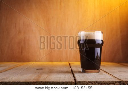 Nonic pint glass with black stout beer on a grunge wood background